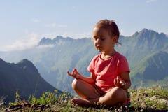 Weinig leuk meisje die bovenop berg mediteren Royalty-vrije Stock Fotografie