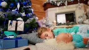 Weinig leuk meisje die een pop tijdens slaap, de kindslaap dichtbij een Kerstboom, zoete slaap in de woonkamer koesteren stock videobeelden