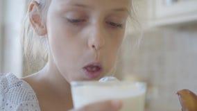 Weinig leuk meisje die een stuk pasteitje en dranken afbijten het neer met melk, onderzoekt dan de camera, glimlachend en toont stock footage
