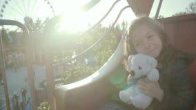 Weinig leuk meisje die en haar teddybeer houden koesteren terwijl zij die een carrousel berijden stock footage