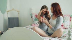 Weinig leuk meisje die giftdoos thuis geven aan haar jonge gelukkige moeder het vieren verjaardagszitting op bed in comfortabele  stock videobeelden