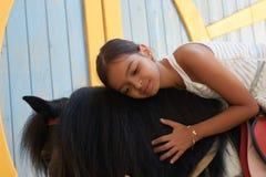 Weinig leuk meisje die haar paardponey koesteren stock foto's