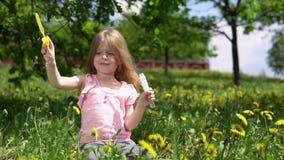 Weinig leuk meisje die met paardebloemen op een de lente zonnige dag spelen stock video