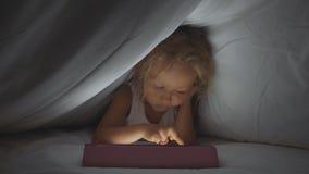 Weinig leuk meisje die onder dekbed liggen en digitaal tabletapparaat met behulp van bij bedtijd stock footage