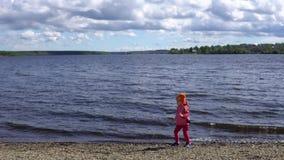 Weinig leuk meisje die op de kust van een vijver met rotsen spelen stock video