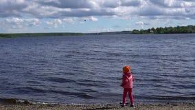 Weinig leuk meisje die op de kust van een vijver met rotsen spelen, langzame motie stock footage