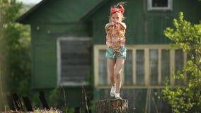 Weinig leuk meisje die op een stomp in de werf van een buitenhuis dansen gelukkig stock video