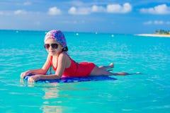 Weinig leuk meisje die op een surfplank in zwemmen royalty-vrije stock afbeelding