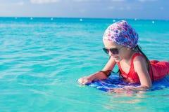 Weinig leuk meisje die op een surfplank in zwemmen royalty-vrije stock afbeeldingen