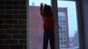 Weinig leuk meisje die zich op de venstervensterbank bevinden, die uit op sneeuwcityscape kijken stock videobeelden