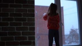 Weinig leuk meisje die zich op de venstervensterbank bevinden, die uit op sneeuwcityscape kijken stock footage