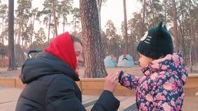Weinig leuk meisje in een kleurrijk roze jasje trekt met een jonge moeder met krijt op een bestrating dichtbij de speelplaats in  stock footage