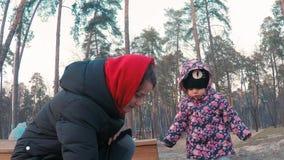 Weinig leuk meisje in een kleurrijk roze jasje trekt met een jonge moeder met krijt op een bestrating dichtbij de speelplaats in  stock videobeelden