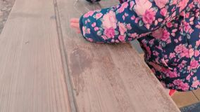 Weinig leuk meisje in een kleurrijk roze jasje trekt met krijt op een bank dichtbij de speelplaats van de kinderen in het park op stock video