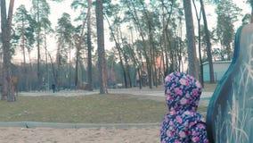Weinig leuk meisje in een kleurrijk roze jasje trekt met krijt op een bord in de vorm van een dinosaurus op kinderen stock video