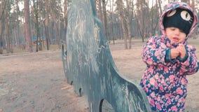 Weinig leuk meisje in een kleurrijk roze jasje trekt met krijt op een bord in de vorm van een dinosaurus op kinderen stock videobeelden