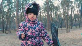 Weinig leuk meisje in een kleurrijk roze jasje trekt met krijt op een bord in de vorm van een dinosaurus op kinderen stock footage