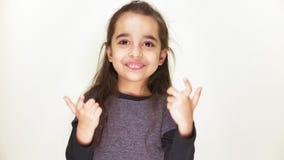 Weinig leuk meisje glimlacht en tonend een teken, kom hier, portret, witte achtergrond 50 fps stock video