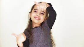 Weinig leuk meisje glimlacht en toont als teken, aardig goedkeuren, o.k., portret, witte achtergrond 50 fps stock videobeelden