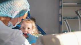 Weinig leuk meisje in het tandarts` s bureau wil niet, zich verzet en sluitend tegen haar mond met haar handen worden behandeld stock video