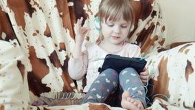 Weinig leuk meisje kijkt beeldverhalen op digitaal lusje stock videobeelden