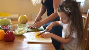 Weinig leuk meisje leert om groenten van haar moeder te snijden Het meisje kijkt zorgvuldig en herhaalt stock video