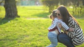 Weinig Leuk Meisje loopt aan haar Moeder die van Sunny Day Outdoors genieten De jonge Vrouw en de Dochter koesteren en spelen stock videobeelden