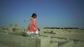 Weinig leuk meisje loopt op de muur in grote amphitheatre Het kind heeft een droom Jong geitjesprongen van omheining Roze kleding stock footage