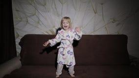 Weinig leuk meisje met blond haar springt op bank Badjaskleren gelukkig stock videobeelden