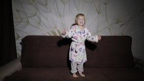 Weinig leuk meisje met blond haar springt op bank Badjaskleren gelukkig stock video