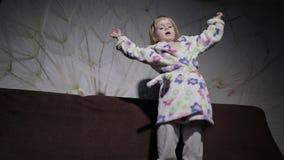 Weinig leuk meisje met blond haar springt op bank Badjaskleren gelukkig stock footage