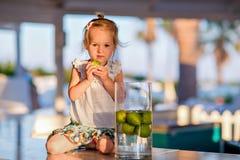 Weinig leuk meisje met citrusvruchten in hand zitting op de lijst stock foto
