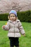 Weinig leuk meisje met gele bloemen in het park van de bloesemlente Stock Fotografie