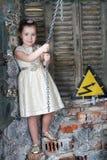 Weinig leuk meisje in mooie kledingsgreep door grote metaalketting Stock Afbeelding