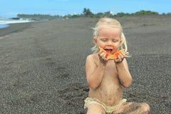 Weinig leuk meisje op het overzeese strand die rijpe papaja eten royalty-vrije stock afbeeldingen