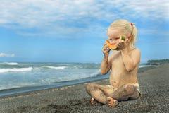 Weinig leuk meisje op het overzeese strand die rijpe papaja eten royalty-vrije stock afbeelding