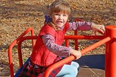 Weinig leuk meisje in rood vest zit en berijdt op carrousel royalty-vrije stock afbeeldingen