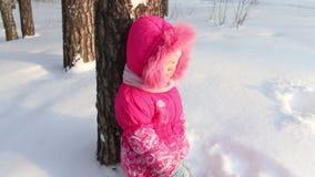 Weinig leuk meisje in roze bevindt zich dichtbij boom bij bos in de winter stock video