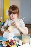 Weinig leuk meisje schildert gipsbeeldje van kat royalty-vrije stock foto