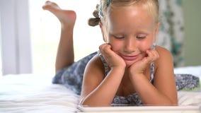 Weinig leuk meisje speelt een spel op de tablet stock video