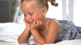Weinig leuk meisje speelt een spel op de tablet stock videobeelden