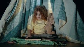 Weinig leuk meisje in tipitent in slaapkameravond stock video