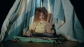 Weinig leuk meisje in tipitent in slaapkameravond stock videobeelden