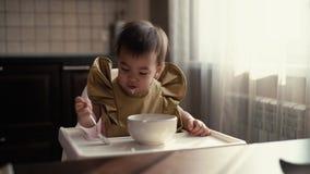 Weinig leuk meisje zit achter een stoel van kinderen en speelt met voedsel stock videobeelden