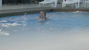 Weinig leuk meisje zwemt in een mooie pool bij een dure toevlucht Recreatie en vrije tijd in openlucht Langzame Motie stock videobeelden