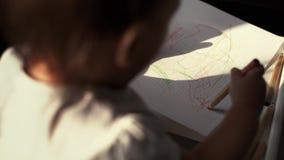Weinig leuk meisjesjong geitje trekt onafhankelijk een potlood op document dichte omhooggaand stock footage