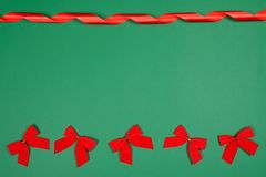 Weinig leuk rood buigt en zijdeachtig getold lint op groene backround met een ruimte voor tekst stock afbeeldingen