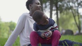 Weinig leuke Afrikaanse Amerikaanse jongen die met plastic stuk speelgoed in het park spelen, die op de overlappingen van de moed stock footage