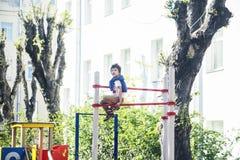 Weinig leuke blonde jongen die buiten op speelplaats hangen die, alleen met pret, het concept van levensstijlkinderen opleiden royalty-vrije stock fotografie