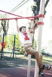 Weinig leuke blonde jongen die buiten op speelplaats hangen die, alleen met pret, het concept van levensstijlkinderen opleiden stock foto